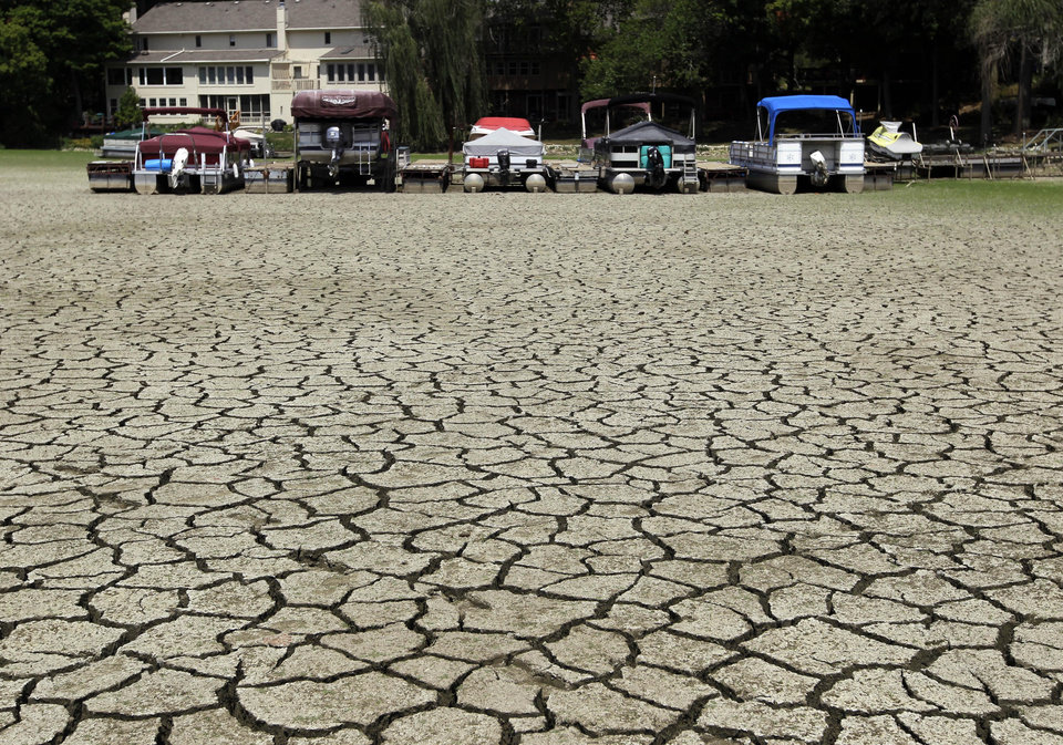 Photo -   Boats sit on the dry, cracked bottom in a dry cove at Morse Reservoir in Noblesville, Ind., Monday, July 16, 2012. The reservoir is down nearly 6 feet from normal levels and being lowered 1 foot every five days to provide water for Indianapolis. (AP Photo/Michael Conroy)