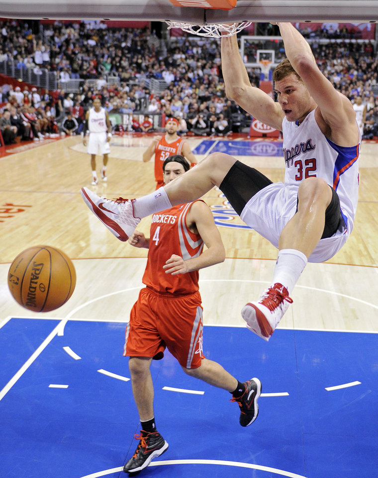 Photo - Los Angeles Clippers forward Blake Griffin, right, dunks the ball as Houston Rockets forward Luis Scola (4) of Argentina looks on during the first half of their NBA basketball game, Wednesday, Dec. 22, 2010, in Los Angeles. (AP Photo/Mark J. Terrill)