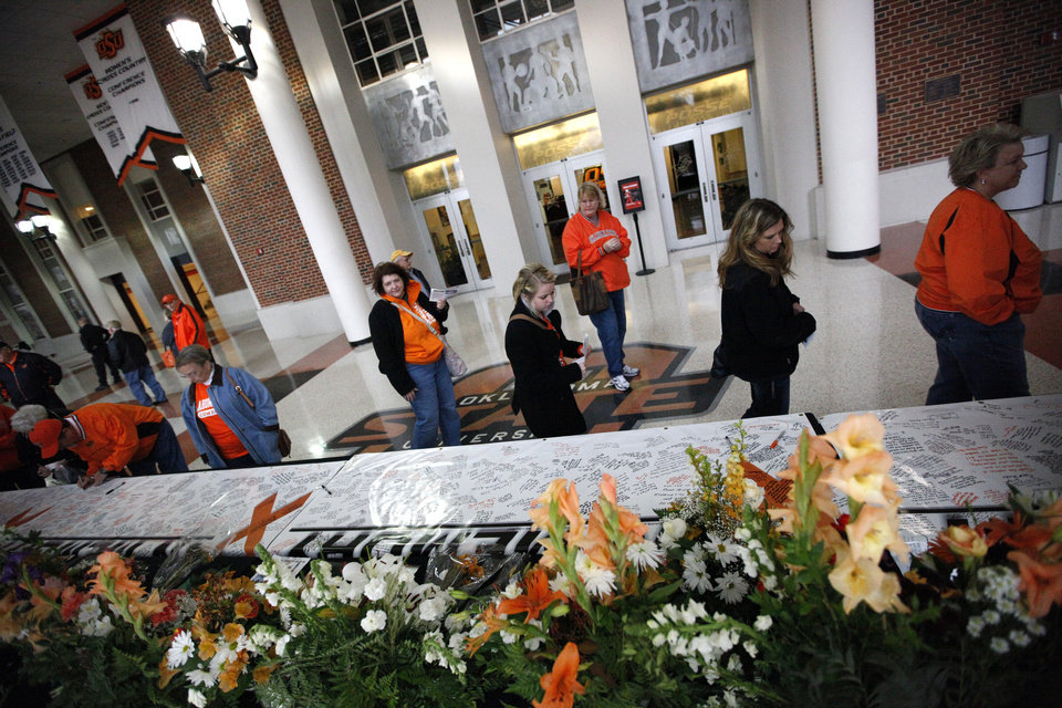 Photo - Fans walk by a memorial before the women's college game between Oklahoma State University and Coppin State at Gallagher-Iba Arena in Stillwater, Okla.,  Saturday, Nov. 26, 2011.  Photo by Sarah Phipps, The Oklahoman