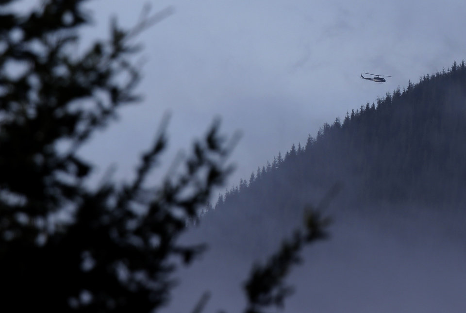Photo - A King Co. Sheriff's Dept. helicopter flies over rugged terrain, Friday, Jan. 4, 2013, near Mount Si in North Bend, Wash. Searchers in the air and on the ground were looking for 29-year-old Kurt Ruppert, who has been missing since a skydiving trip on Thursday. (AP Photo/Ted S. Warren)