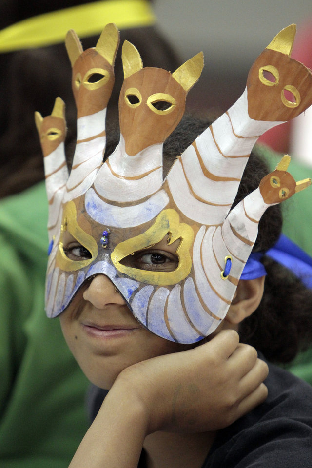 Photo - Janelle Downing, 13, dons a mask made by Patrick Riley at a mask-making workshop at Norman Public Library.