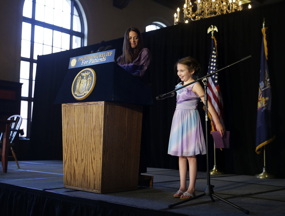 Photo - Amanda Houser, 10, and her mother Maryanne Houser speak during a ceremonial bill signing for medical marijuana in New York, Monday, July 7, 2014. New York has become the 23rd state in the U.S. to authorize medical marijuana, though the state's program is one of the nation's most restrictive. Gov. Andrew Cuomo signed the measure into law on Saturday and held the formal signing ceremony on Monday to highlight the new law.  When the program gets up and running in about 18 months, patients with diseases including AIDS, cancer and epilepsy will be able to obtain non-smokeable versions of the drug. Instead, the drug must be ingested or administered through a vaporizer or oil base. Houser, who has Dravet syndrome, may benefit from medical marijuana.(AP Photo/Seth Wenig)