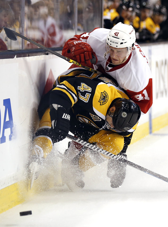 Photo - Boston Bruins defenseman Torey Krug (47) stops Detroit Red Wings' Luke Glendening (41) from getting around him during the first period of Game 2 of a first-round NHL hockey playoff series in Boston, Sunday, April 20, 2014. (AP Photo/Winslow Townson)