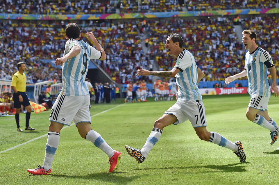 Photo - Argentina's Gonzalo Higuain, left, celebrates with Angel di Maria, center, and Lionel Messi after he scored the opening goal during the World Cup quarterfinal soccer match between Argentina and Belgium at the Estadio Nacional in Brasilia, Brazil, Saturday, July 5, 2014. (AP Photo/Martin Meissner)