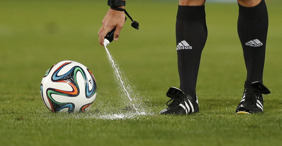 Photo - FILE - In this Wednesday, Dec. 18, 2013, file photo, referee Carlos Velasco of Spain marks a line with vanishing spray during the semi final soccer match between Raja Casablanca and Atletico Mineiro at the Club World Cup soccer tournament in Marrakech, Morocco. For the first time at a World Cup, technology will be used to determine whether a ball crosses the goal line during matches at the upcoming tournament in Brazil. With vanishing spray also being used to prevent encroachment by defenders making up a wall during free kicks, officials at the highest level of the world's most popular sport are finally getting some assistance. (AP Photo/Matthias Schrader, File)