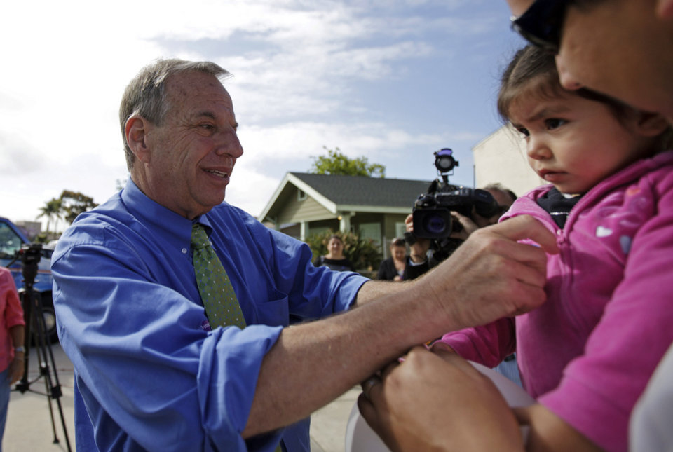 FILE - In this June 5, 2012 file photo, then San Diego mayoral candidate and U.S. Rep. Bob Filner puts a sticker on Izel Alvarez, 2, after casting his ballot on primary election day. After winning that race, Filner is now leaving office in disgrace amid sexual harassment allegations and many unanswered questions, including how someone who acknowledged mistreating women for many years could have survived for so long in politics. (AP Photo/Gregory Bull, File)