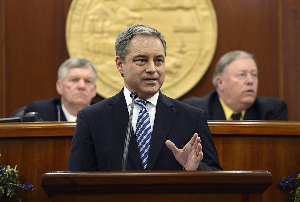 Alaska's Republican Gov. Sean Parnell, center, leads a round of applause for U.S. service members in front of the Alaska State Legislature during his annual State of the State address in Juneau, Alaska Wednesday, Jan. 16, 2013. Also pictured at left, Senate President Charlie Huggins, R- Wasilla, and House Speaker Mike Chenault, R- Nikiski. (AP Photo/Chris Miller)codes