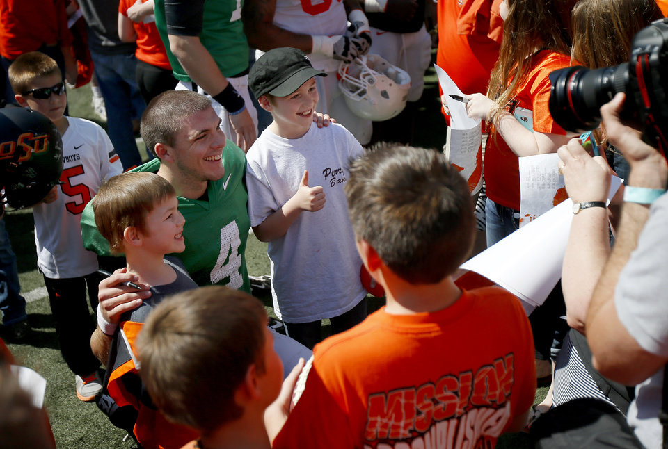 Photo - OSU's J.W. Walsh poses for a photo with fans after Oklahoma State's Orange Blitz football practice at Boone Pickens Stadium in Stillwater, Okla., Saturday, April 5, 2014.
