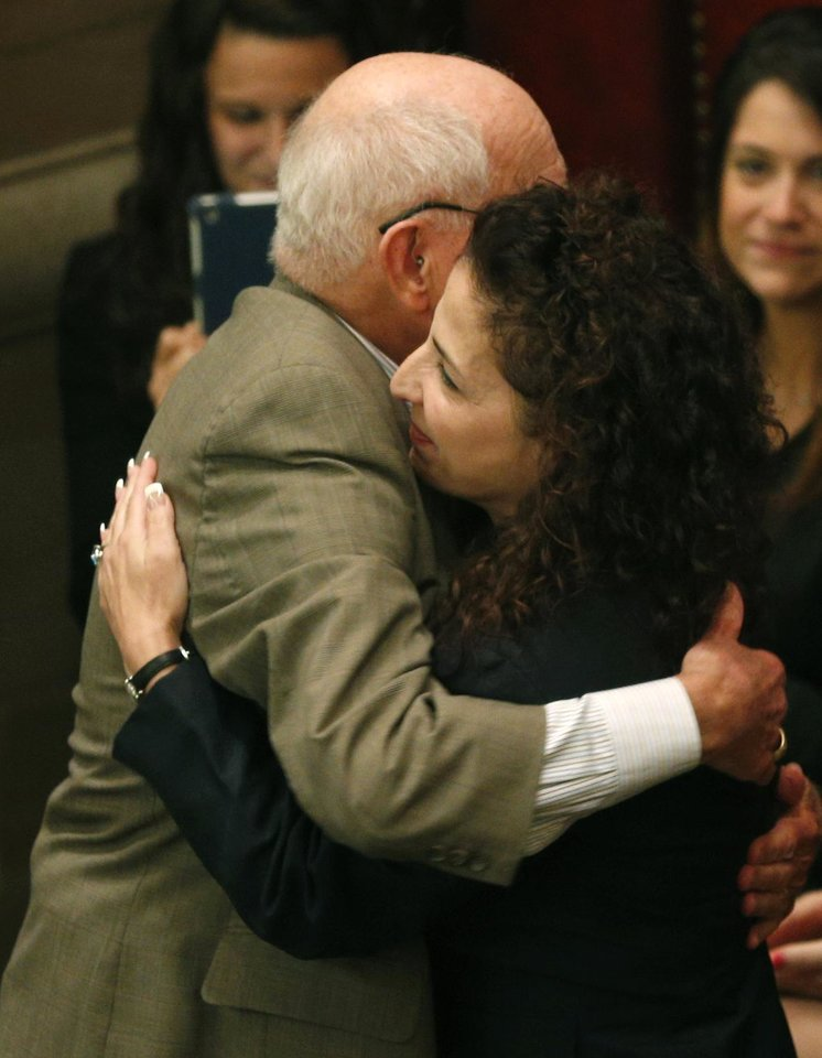 Photo - Sen. William Larkin Jr, R-New Windsor, left, and Sen. Diane Savino, D-Staten Island, hug after the Senate voted to legalize medical marijuana at the Capitol on Friday, June 20, 2014, in Albany, N.Y. Savino sponsored the legislation.  The 49-10 approval follows the 113-13 vote earlier Friday by the Assembly for the compromise among legislative leaders and Gov. Andrew Cuomo. That will make New York the 23rd state to legalize, but the drug won't be available in New York for at least 18 months while regulations are written and five state-approved producers and distributors are chosen. (AP Photo/Mike Groll)