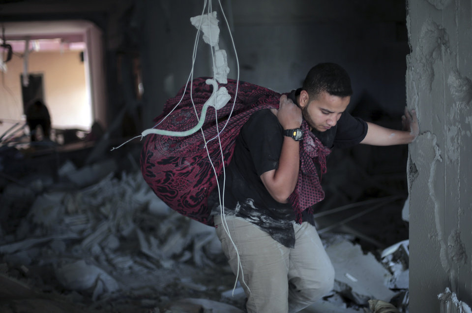 Photo - Palestinians salvage what they can of their belongings from the rubble of their destroyed house following an early morning Israeli missile strike in Gaza City Wednesday, July 16, 2014. Israel on Wednesday intensified air attacks on Hamas targets in the Gaza Strip following a failed Egyptian cease-fire effort, targeting the homes of four senior leaders of the Islamic militant movement and ordering tens of thousands of residents to evacuate border areas. (AP Photo/Khalil Hamra)