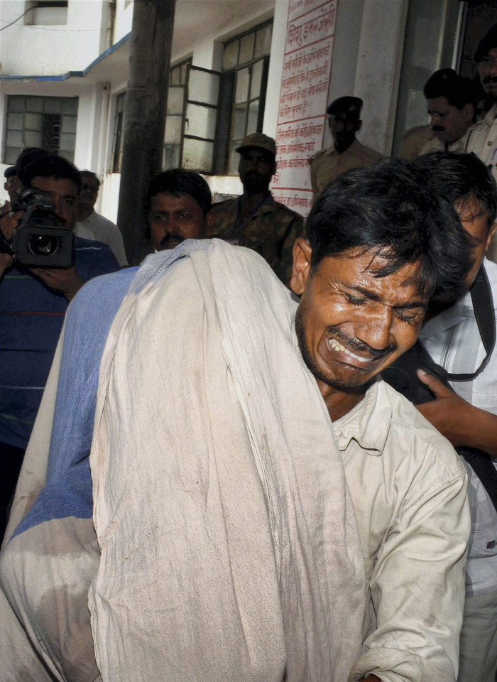 Photo - An Indian man cries while carrying the body of his daughter who died after eating a free school lunch at a hospital in Patna, India, Wednesday, July 17, 2013. At least 21 children died and more than two dozen others were sick after eating a free school lunch that was tainted with insecticide, in Gandamal village in Masrakh block, 80 kilometers (50 miles) north of Patna. (AP Photo) INDIA OUT