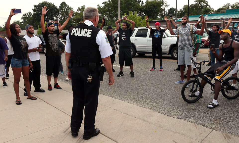 Photo - Protestors blocking Florissant Road raise their hands after being approached by police officers who asked them to stop blocking the street in front of the Ferguson police department on Sunday, Aug. 10, 2014, one day after a Ferguson officer shot and killed Michael Brown. Officers backed down and instead barricaded the street in both directions. (AP Photo/St. Louis Post-Dispatch, Robert Cohen)