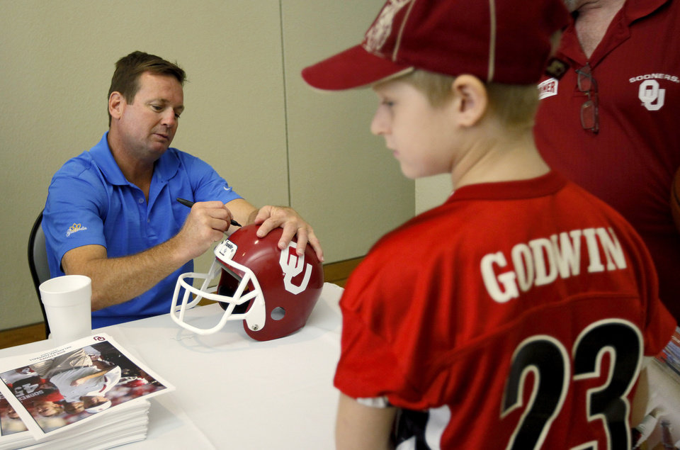 Photo - UNIVERSITY OF OKLAHOMA / COLLEGE FOOTBALL / CHILDREN / KIDS / FANS: OU football coach Bob Stoops signs a helmet for Zac Godwin, 9, of Yukon, Okla., during the 2009 Sooner Caravan stop at the National Cowboy & Western Heritage Museum in Oklahoma City, Thursday, August 6, 2009. Photo by Bryan Terry, The Oklahoman ORG XMIT: KOD