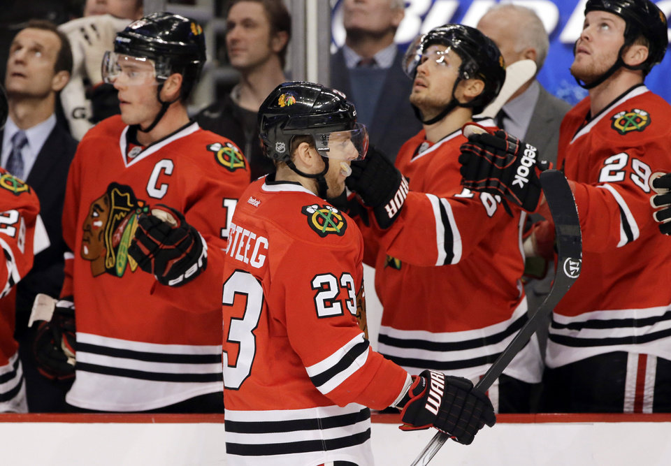 Photo - Chicago Blackhawks' Kris Versteeg (23) is congratulated by teammates after his goal during the first period of an NHL hockey game against the Anaheim Ducks in Chicago, Friday, Jan. 17, 2014. (AP Photo/Nam Y. Huh)