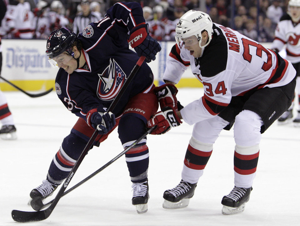 Columbus Blue Jackets' Cam Atkinson, left, carries the puck across the blue line as New Jersey Devils' Jon Merrill defends during the second period of an NHL hockey game Tuesday, Dec. 10, 2013, in Columbus, Ohio. (AP Photo/Jay LaPrete)