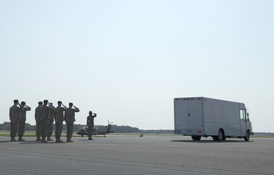 Photo - An Army carry team salutes as the remains of Army Maj. Gen. Harold Greene are driven off the flight line, Thursday, Aug. 7, 2014, at Dover Air Force Base, Del. Greene was shot to death Tuesday when a gunman dressed as an Afghan soldier turned on ISAF troops, wounding about 15 including a German general and two Afghan generals. He is the highest-ranking U.S. military officer to be killed in either of America's post-9/11 wars. (AP Photo/Evan Vucci)