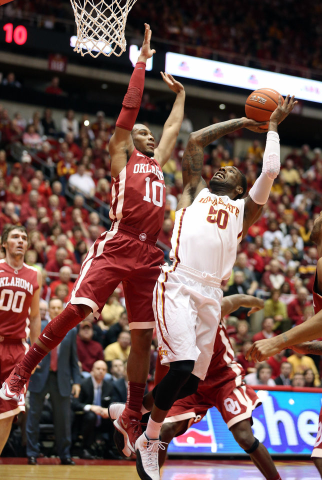 Photo - Oklahoma guard Jordan Woodard (10) tries to block the shot of Iowa State guard DeAndre Kane (50) during the first half of an NCAA college basketball game in Ames, Iowa, Saturday, Feb. 1, 2014. (AP Photo/Justin Hayworth)