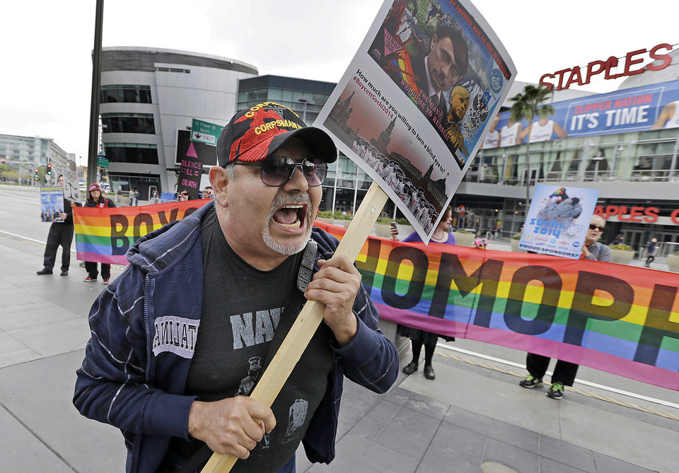Photo - Dave Lara, of Los Angeles, joins demonstrators from a coalition of gay rights organizations, religious and political groups protest the treatment of gays in Russia, whose coastal city of Sochi hosts the 22nd Olympic Winter Games, outside the final stop of the
