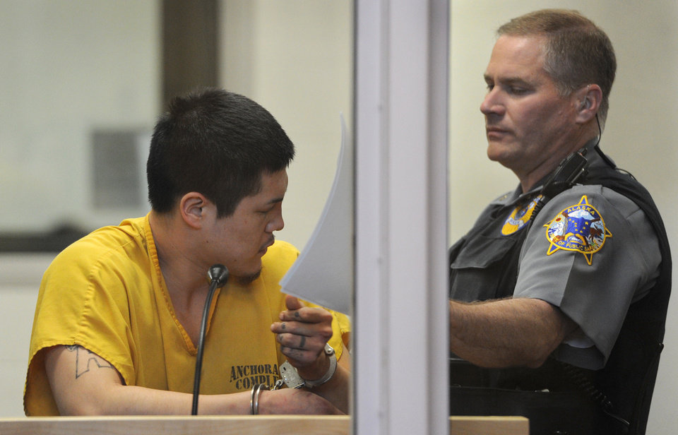 Photo - An officer in the Anchorage jail court removes the paperwork that Jerry Andrew Active was using to shield his face during his arraigned on charges of murder and sexual assault of a minor on Sunday, May 26, 2013 in Anchorage, Alaska. Active was arrested about a block from an apartment where the bodies of 71-year-old Sorn Sreap and 73-year-old Touch Chea were found Saturday night by their granddaughter, who had returned from a trip to a movie with her husband and 4-year-old son. (AP Photo/Anchorage Daily News, Bill Roth)