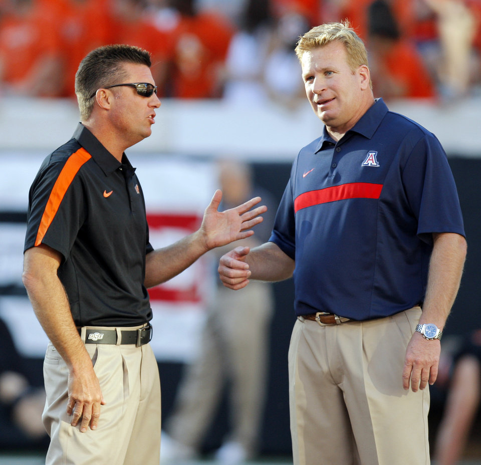Photo - OSU head coach Mike Gundy, left, and Arizona head coach Mike Stoops talk before a college football game between the Oklahoma State University Cowboys (OSU) and the University of Arizona Wildcats at Boone Pickens Stadium in Stillwater, Okla., Thursday, Sept. 8, 2011. Photo by Nate Billings, The Oklahoman  ORG XMIT: KOD
