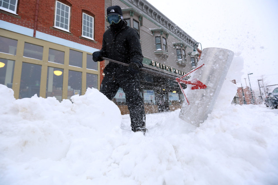 Photo - Earl Barnes shovels snow off the sidewalk in front of Smith's Market on S. Main St. in Hutchinson, Kan., Tuesday, Feb. 4, 2014. The winter storm dumped more than 10 inches of snow on the city from late Monday to late Tuesday. (AP Photo/The Hutchinson News, Travis Morisse)