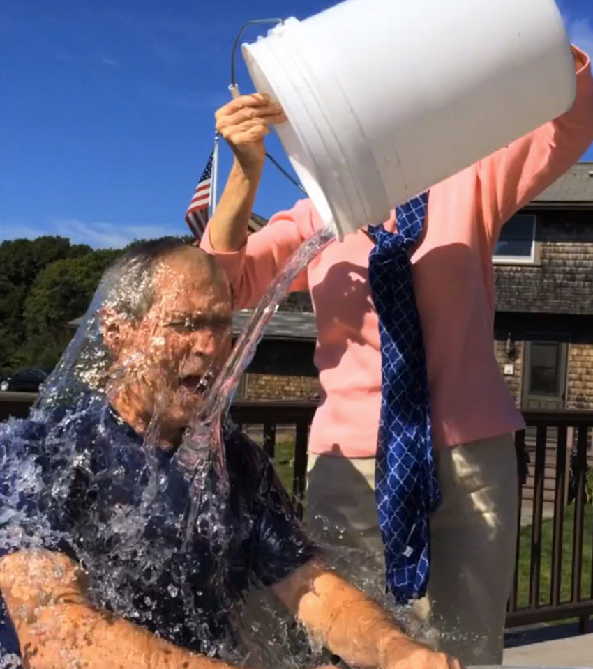Photo - In this image from video posted on Facebook, courtesy of the George W. Bush Presidential Center, former President George W. Bush participates in the ice bucket challenge with the help of his wife, Laura Bush, in Kennebunkport, Maine. The challenge has caught on with notable figures participating in the campaign to raise money for the fight against ALS, or Lou Gehrig's disease. (AP Photo/Courtesy George W. Bush Presidential Center)