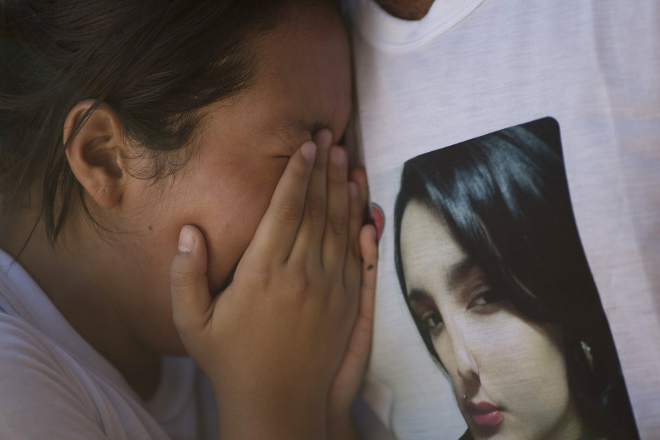 Photo - A young woman weeps as she is embraced by an unidentified man wearing a T-shirt with an image of the crying woman's sister, a victim of the Kiss nightclub fatal fire, during a protest in Santa Maria, Brazil, Tuesday, Jan. 29, 2013. Locals marched through Santa Maria Tuesday to demand justice for the dead. The demonstration interrupted a news conference as the police investigator pledged to investigate everyone involved in the tragedy - including the authorities charged with making sure such establishments are up to code. The fast-moving fire roared through the crowded, windowless Kiss nightclub in this southern Brazilian city early Sunday, killing more than 230 people.  (AP Photo/Felipe Dana)