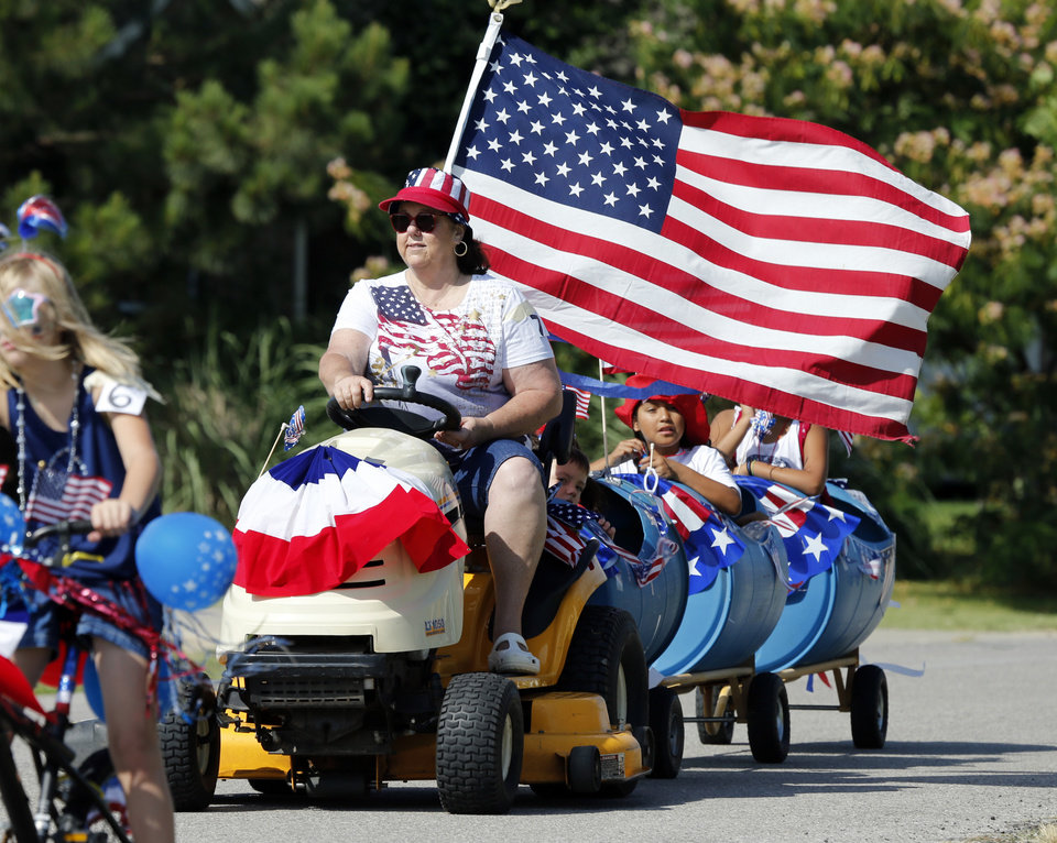 Rhonda Terry drives a lawnmower and pulls her grandchildren ride in a neighborhood July 4th parade in the Remington and Stonebrook additions on Friday, July 4, 2014 in Norman, Okla.  Photo by Steve Sisney, The Oklahoman