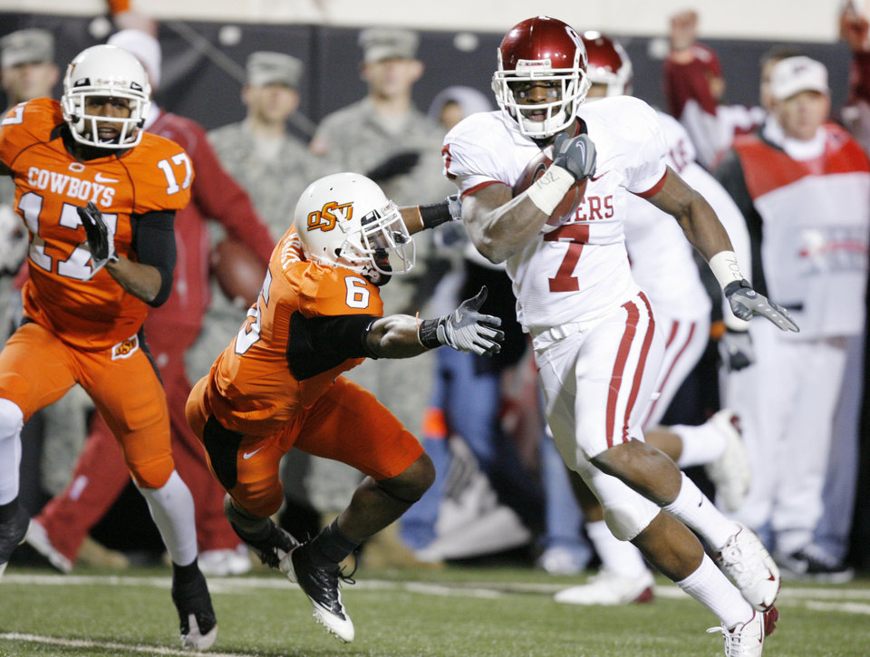 Photo - OU's Demarco Murray runs for a touchdown past Rickey Price (6) and Jacob Lacey (17) of OSU during the first half of the college football game between the University of Oklahoma Sooners (OU) and Oklahoma State University Cowboys (OSU) at Boone Pickens Stadium on Saturday, Nov. 29, 2008, in Stillwater, Okla. STAFF PHOTO BY CHRIS LANDSBERGER