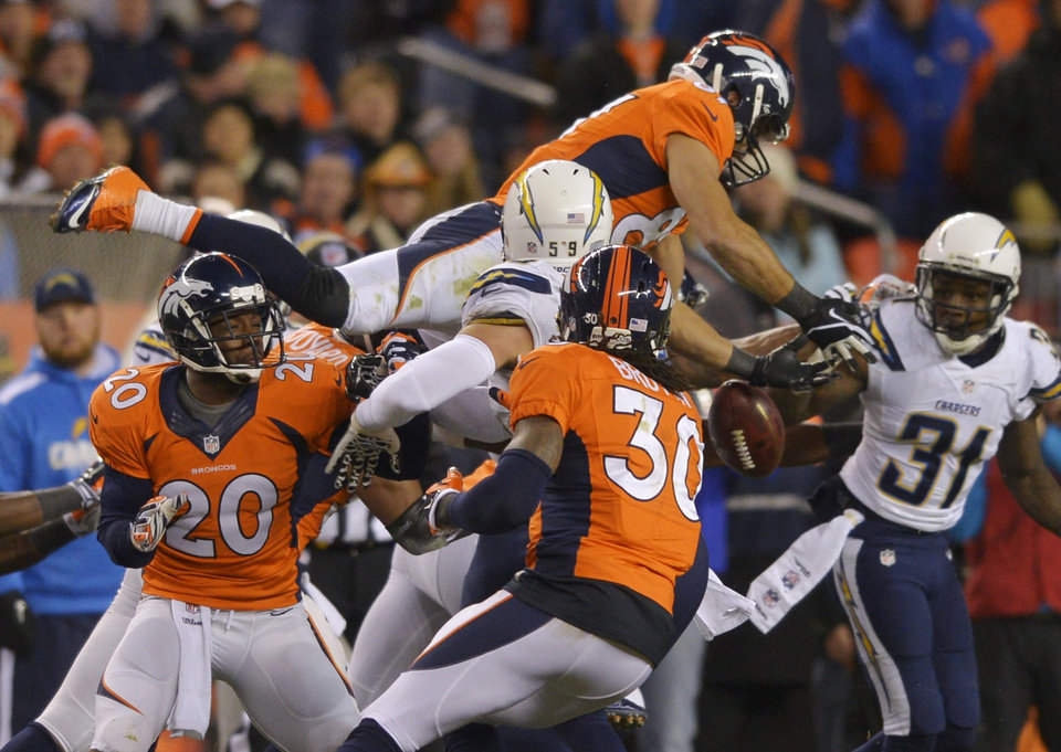 Photo - Denver Broncos wide receiver Eric Decker (87) leaps for an onside kick by thte San Diego Chargers in the fourth quarter of an NFL AFC division playoff football game, Sunday, Jan. 12, 2014, in Denver. San Diego recovered the kick on the play. (AP Photo/Jack Dempsey)
