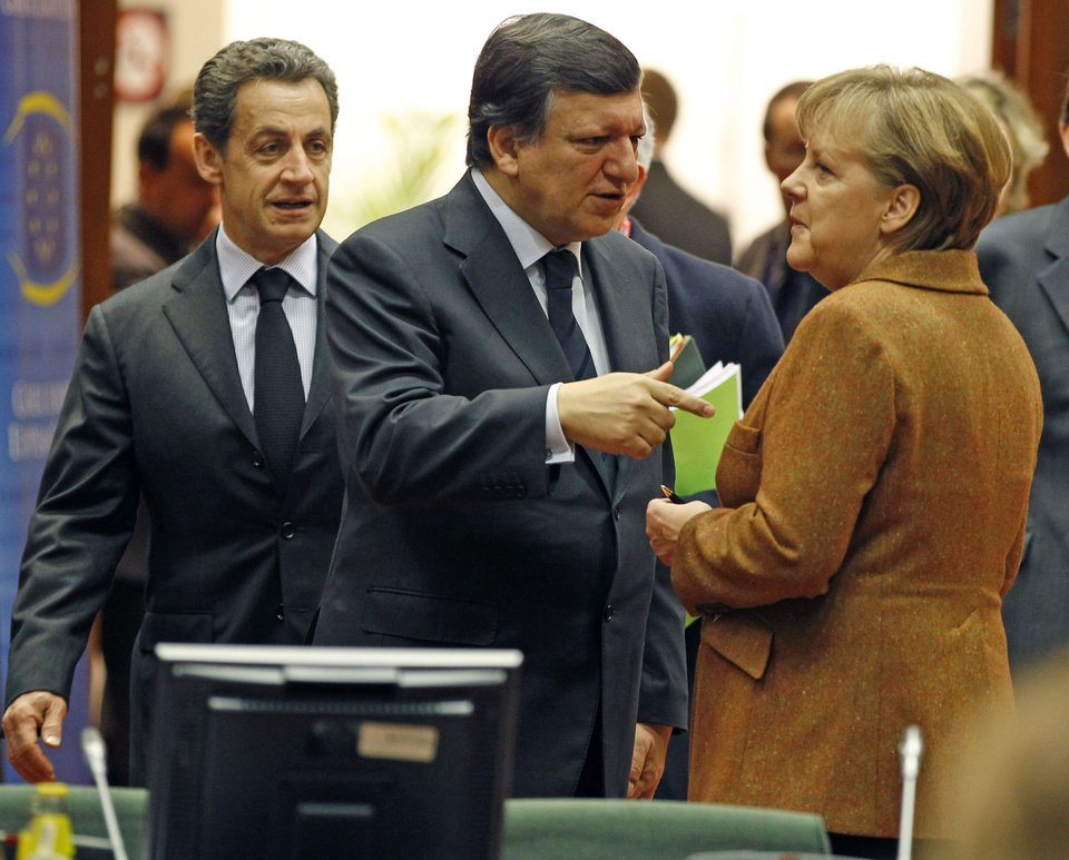 French President Nicolas Sarkozy, left, speaks with European Commission President Jose Manuel Barroso, center, and German Chancellor Angela Merkel during a round table meeting at an EU Summit in Brussels on Friday, March 2, 2012. The leaders of 25 European states have signed a new treaty designed to prevent the 17 euro countries from running up huge debts in order to prevent a repeat of the current crisis afflicting the single currency zone. (AP Photo/Remy de la Mauviniere)