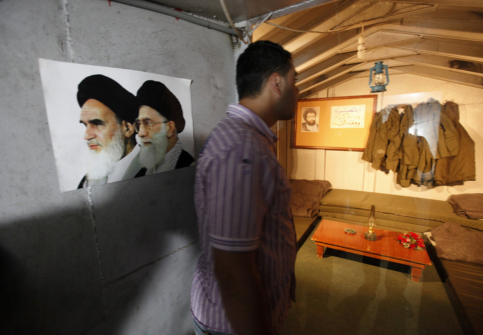 Photo -   FILE - In this Friday May 21, 2010 file photo, a Lebanese man, looks at an underground bunker room used during fighting with Israel, as he stands next to a poster shows the late Iranian revolutionary founder Ayatollah Khomeini, left, and Iran's supreme leader Ayatollah Ali Khamenei, right, at a Hezbollah war museum inaugurated on Friday, in Mlita Village, southern Lebanon. Hezbollah may have suffered setbacks from Syria's civil war, with many Lebanese angry over its backing of President Bashar Assad's regime. But that's unlikely to cost the Shiite militant movement its powerful grip in Lebanon, observers say. The group's overwhelming arsenal is still the foundation of its strength, bolstered by political alliances. (AP Photo/Hussein Malla, File)