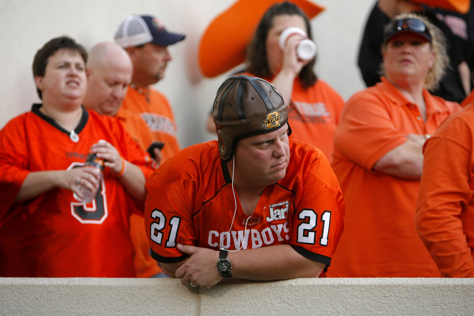 Photo - Fans react during the final minutes of the college football game between the Oklahoma State Cowboys (OSU) and the Nebraska Huskers (NU) at Boone Pickens Stadium in Stillwater, Okla., Saturday, Oct. 23, 2010. Photo by Sarah Phipps, The Oklahoman