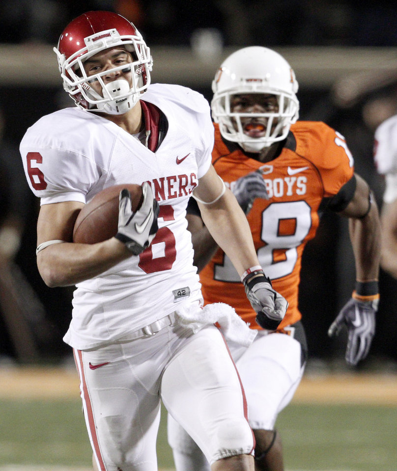 Photo - Oklahoma's Cameron Kenney  (6) scores on a long touchdown pass in front of Oklahoma State's Devin Hedgepeth (18) during the Bedlam college football game between the University of Oklahoma Sooners (OU) and the Oklahoma State University Cowboys (OSU) at Boone Pickens Stadium in Stillwater, Okla., Saturday, Nov. 27, 2010. Photo by Bryan Terry, The Oklahoman