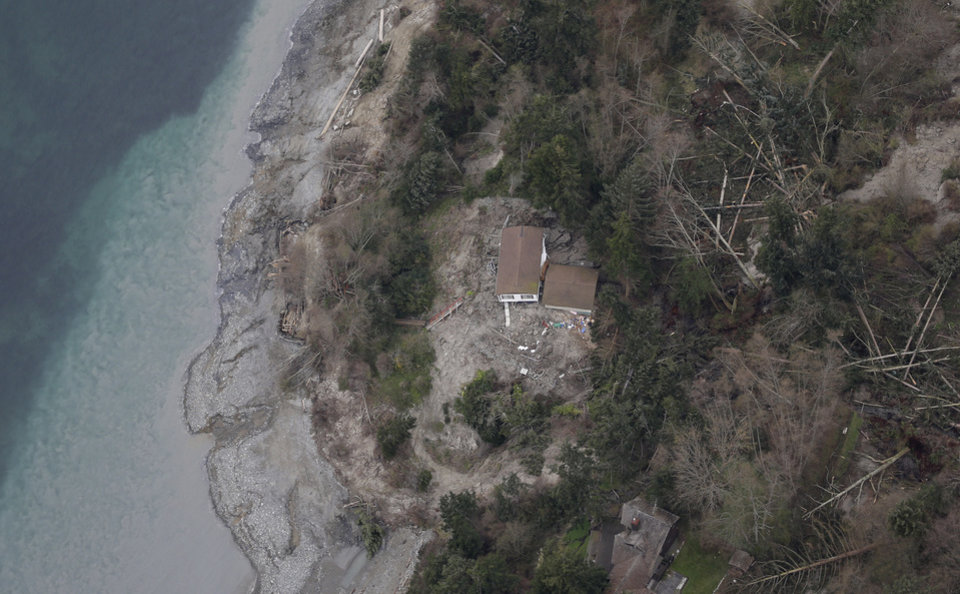 Photo - In this aerial photo, a house sits near the bottom edge of a landslide near Coupeville, Wash. on Whidbey Island, Wednesday, March 27, 2013. The slide severely damaged one home and isolated or threatened more than 30 on the island, about 50 miles north of Seattle in Puget Sound. No one was reported injured in the slide, which happened at about 4 a.m. Wednesday. (AP Photo/Ted S. Warren)