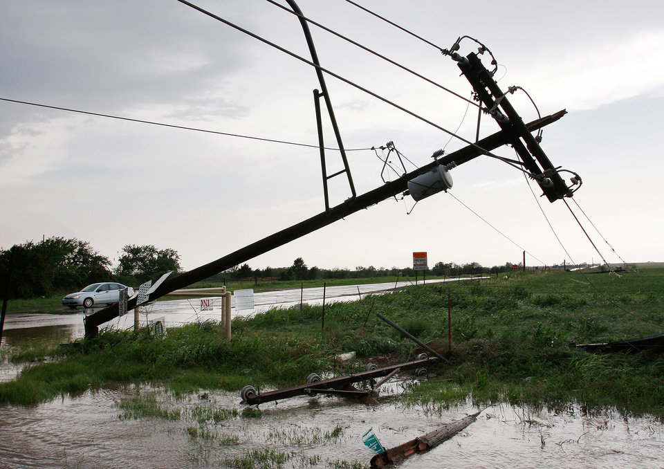 Photo - A toppled utility pole on SH 74, near Cashion. after a tornado came through the area Tuesday afternoon,  May 24, 2011,   Photo by Jim Beckel, The Oklahoman