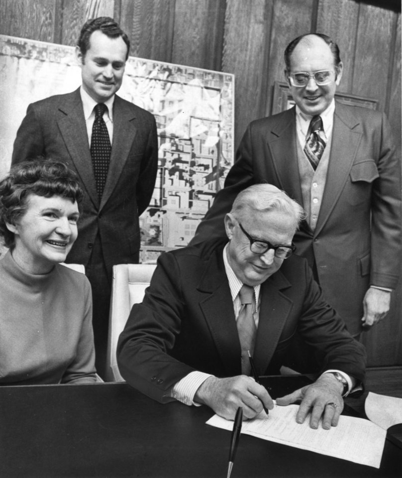 """Pleased Oklahoma City officials watch Robert Breeden place his signature on documents that insure the city will receive $36 million in federal grants for constructing the proposed $100 million Galleria downtown.  Breeden, state director of the U.S. Department of Housing and Urban Development, is flanked by Mayor Patience Latting; Ed Cook, chamber of commerce president, and James White, urban renewal director, at the ceremonial signing of the loan and grant contract."" Staff photo by Bob Albright taken 1/17/74; photo ran in the 1/17/74 Oklahoma City Times."