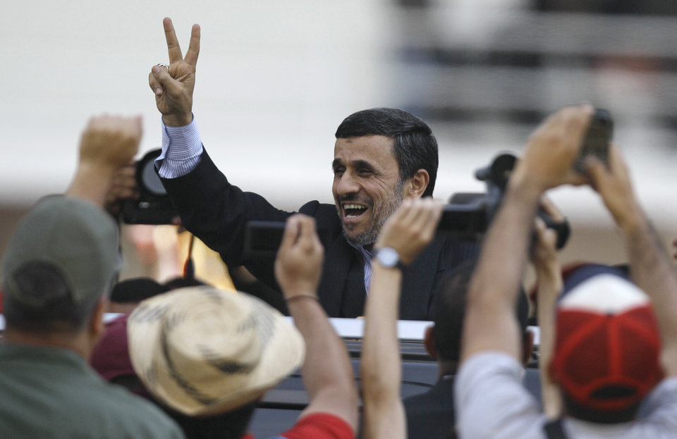 Photo - Iran's President Mahmoud Ahmadinejad makes a victory sign after attending the funeral ceremony for Venezuela's late President Hugo Chavez at the military academy in Caracas, Venezuela, Friday, March 8, 2013. Chavez died on March 5 after a nearly two-year bout with cancer.  He was 58.  (AP Photo/Fernando Llano)