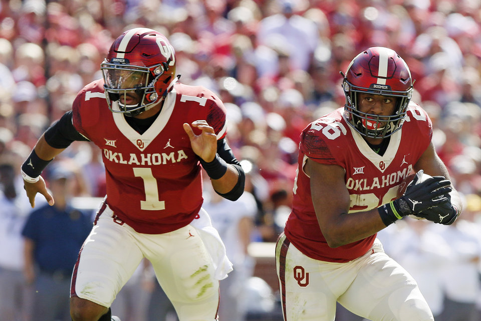 Photo - Oklahoma's Kennedy Brooks (26) carries the ball beside Oklahoma's Jalen Hurts (1) during a college football game between the University of Oklahoma Sooners (OU) and the West Virginia Mountaineers at Gaylord Family-Oklahoma Memorial Stadium in Norman, Okla, Saturday, Oct. 19, 2019. Oklahoma won 52-14. [Bryan Terry/The Oklahoman]