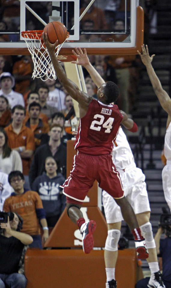 Photo - Oklahoma guard Buddy Hield (24) drives to the basket against Texas forward Connor Lammert during the second half an NCAA college basketball game, Monday, Jan. 5, 2015, in Austin, Texas. Oklahoma won 70-49.  (AP Photo/Michael Thomas)