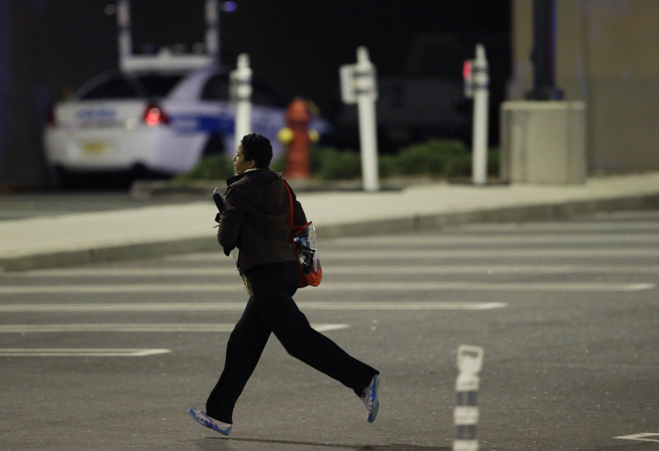 Photo - A woman runs in the parking lot of the Garden State Plaza Mall following reports of a shooter, Monday, Nov. 4, 2013, in Paramus, N.J. Hundreds of law enforcement officers converged on the mall Monday night after witnesses said multiple shots were fired there. (AP Photo/Julio Cortez)