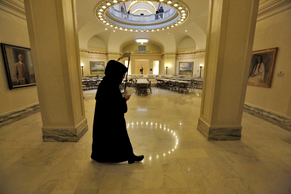 Photo - The 'Grim Reaper' walks in the rotunda of the state Capitol in Oklahoma City, Tuesday February 19, 2013. The 'Reaper' attended Governor Mary Fallin's announcement for plans to put tobacco regulations aimed at reducing second-hand smoke to a vote of the people. Photo By Steve Gooch, The Oklahoman