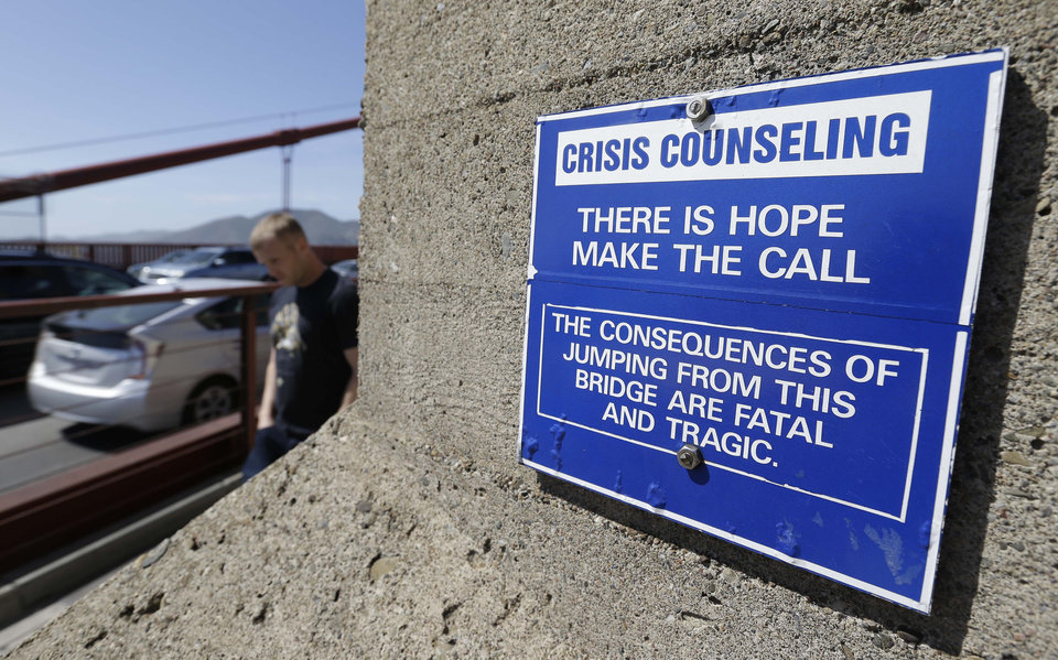 Photo - FILE - In this file photo taken Tuesday, April 30, 2013, a sign is posted above a crisis counseling call box on the Golden Gate Bridge in San Francisco. On Friday, June 27, 2014, Golden Gate Bridge officials are expected to approve a funding package for a $76 million suicide barrier. (AP Photo/Eric Risberg)