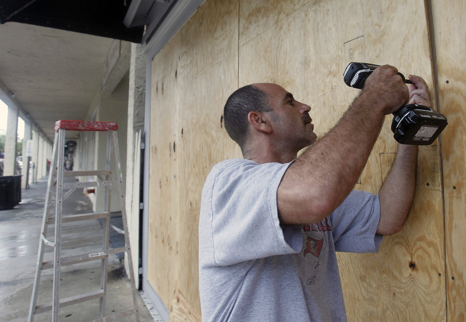 Photo -   Oren Eshel boards a storefront on Duval Street in Key West, Fla., Saturday, Aug. 25, 2012 in preparation for Tropical Storm Isaac, Saturday, Aug. 25, 2012. Isaac's winds are expected to be felt in the Florida Keys by sunrise Sunday morning. (AP Photo/Alan Diaz)