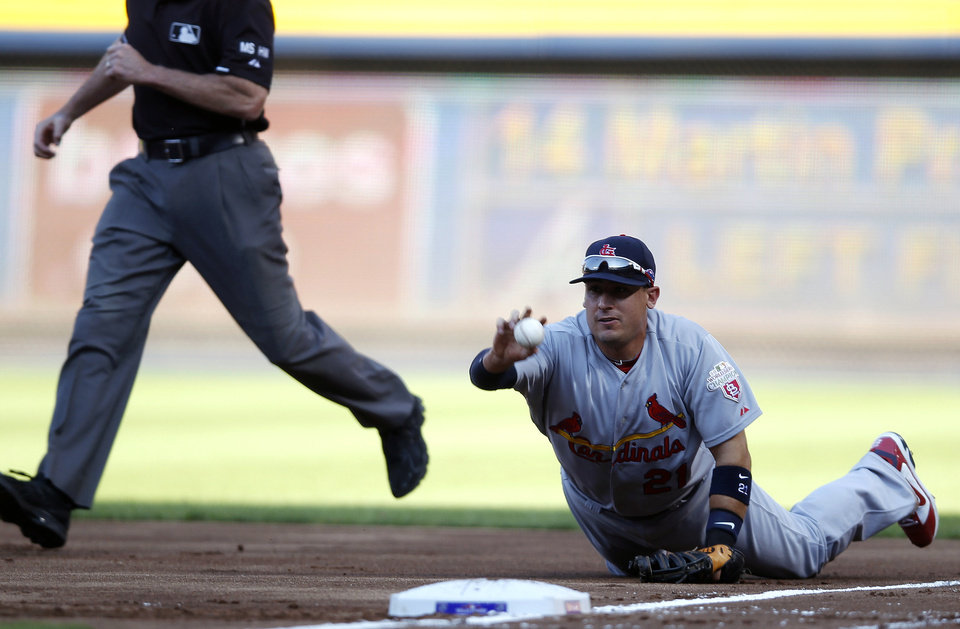 Photo -   St. Louis Cardinals first baseman Allen Craig, right, tosses an Atlanta Braves' Martin Prado-hit ball to Cardinals starting pitcher Kyle Lohse for an out during the National League wild card playoff baseball game on Friday, Oct. 5, 2012, in Atlanta. (AP Photo/John Bazemore)