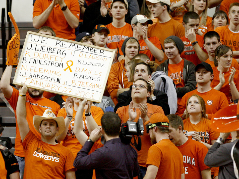 Photo - OSU fans hold a sign in honor of those who dies in a plane crash on January 27, 2001, during an NCAA college basketball game between the Oklahoma State University and Texas A&M at Gallagher-Iba Arena in Stillwater, Okla., Wednesday, January 27, 2010. Photo by Bryan Terry, The Oklahoman