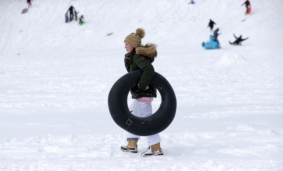 Photo - Layne Peterson walks with an inter tube while sledding on a hill along Hefner Road in Oklahoma City, Wednesday, Feb. 17, 2021. [Sarah Phipps/The Oklahoman]