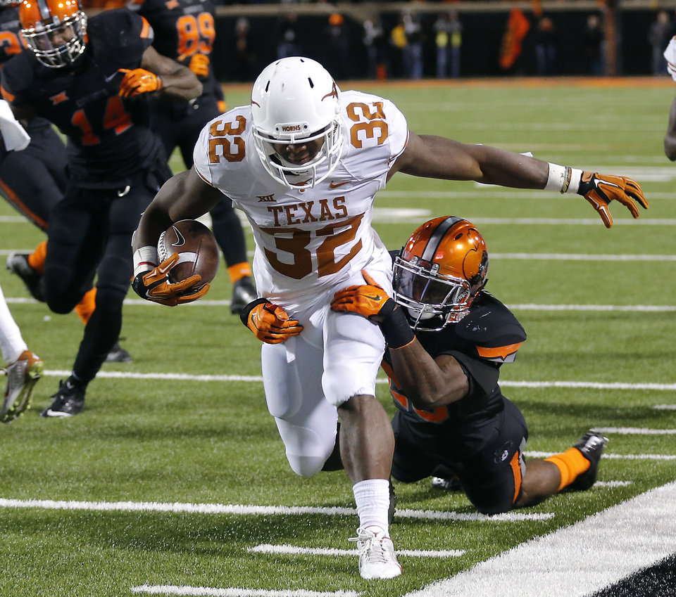 Photo - Texas' Johnathan Gray (32) drags Oklahoma State's Larry Stephens (20) down the sideline during the college football game between the Oklahoma State University Cowboys (OSU) the University of Texas Longhorns (UT) at Boone Pickens Staduim in Stillwater, Okla. on Saturday, Nov. 15, 2014.  Photo by Chris Landsberger, The Oklahoman