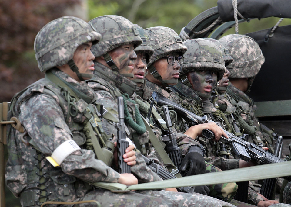 Photo - South Korean army soldiers on the truck head to search for a South Korean conscript soldier who is on the run after a shooting incident in Goseong, South Korea, Sunday, June 22, 2014. South Korean military authorities have surrounded a soldier who fled his border outpost after killing five comrades the day before and were trying to persuade him to surrender, a defense official said Sunday.(AP Photo/Ahn Young-joon)