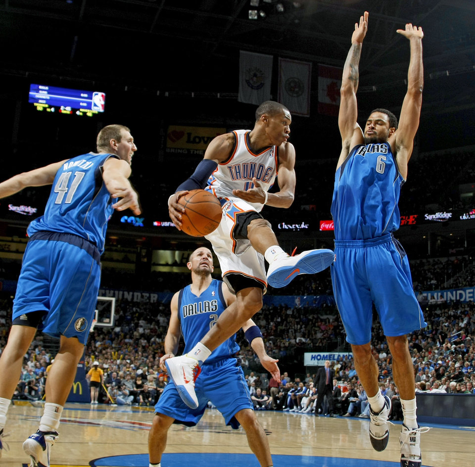 Oklahoma City's Russell Westbrook goes between Dirk Nowitzki, left, Jason Kidd, and Tyson Chandler of Dallas during the NBA basketball game between the Oklahoma City Thunder and the Dallas Mavericks at the Oklahoma City Arena on Wednesday, Nov. 24, 2010.   Photo by Bryan Terry, The Oklahoman